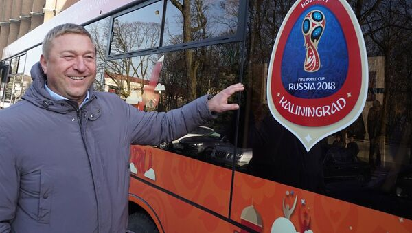 Primátor města Alexandr Jarušuk u městského autobusu Kaliningradu se symboly světového šampionátu ve fotbale roku 2018. - Sputnik Česká republika