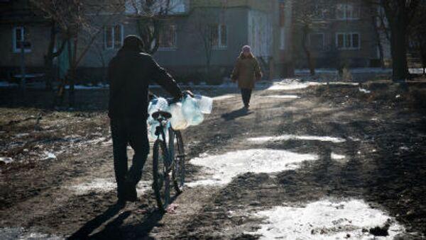 Muž jde pro pitnou vodu v městě Debalceve - Sputnik Česká republika
