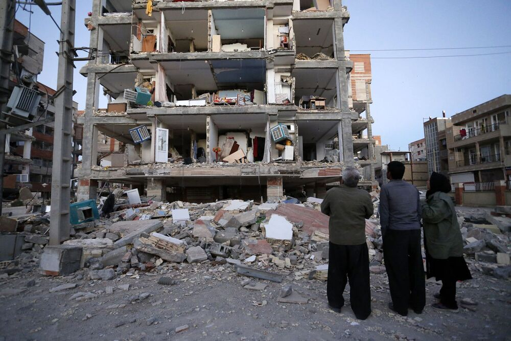 Lidé se dívají na zbořenou budovu po zemětřesení v městě Sere-Pole-Zohab, Írán