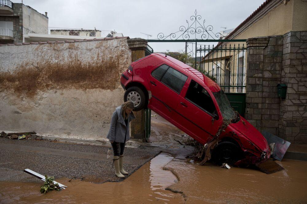 Žena u auta uneseného záplavou v Aténách, Řecko