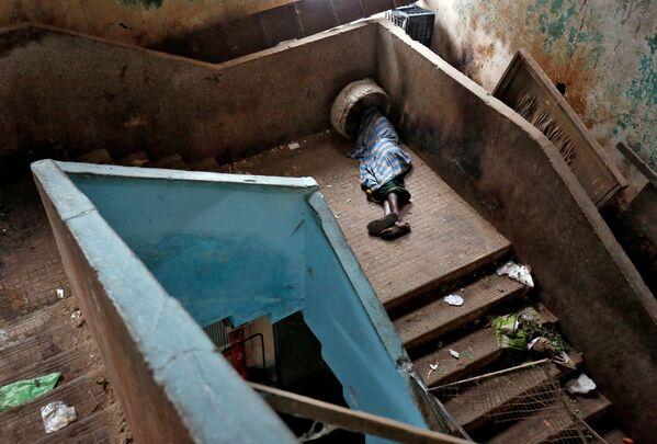 Žebrák spí na schodech ve velkoobchodní tržnici v Bangalore, Indie - Sputnik Česká republika