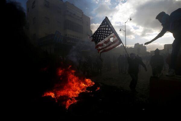 Palestinci spalují americkou vlajku během srážek s izraelskou policií kvůli protestům proti rozhodnutí Donalda Trumpa o uznání Jeruzalému za hlavní město Izraele - Sputnik Česká republika