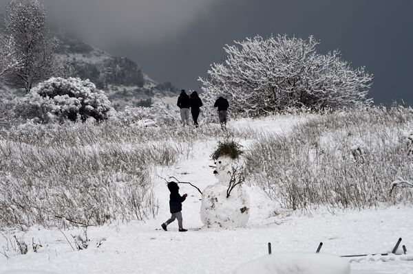 Dítě vedle sněhuláku v okolí francouzského města Marseille - Sputnik Česká republika