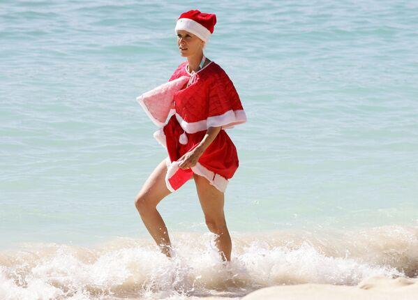 Žena v kostýmu Santa Klause na pláži Guadeloupe - Sputnik Česká republika