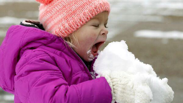 Holčička jí sníh ve městě Jackson státu Mississippi - Sputnik Česká republika
