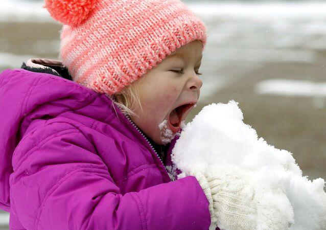Holčička jí sníh ve městě Jackson státu Mississippi