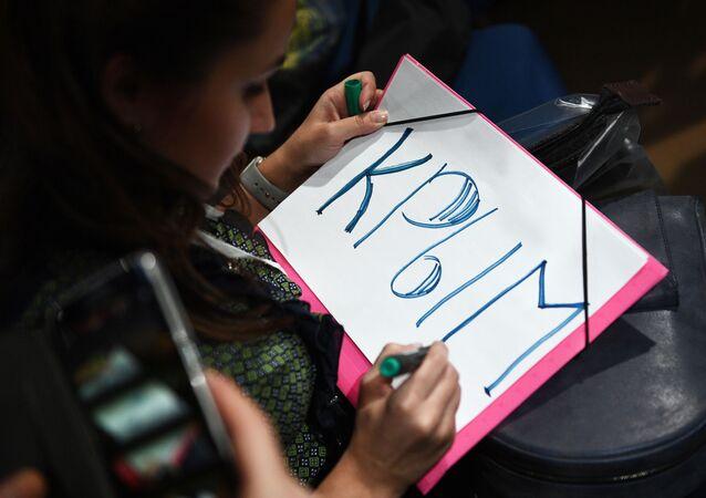 Novinářka píše slovo Krym na plakátu