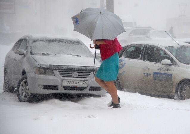 Dívka jde po ulici během silného sněžení