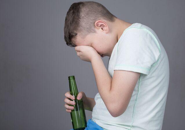 Dítě s lahví alkoholu