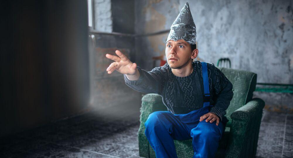Muž v čepici z alobalu naproti televizi