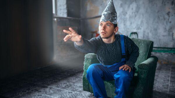Muž v čepici z alobalu naproti televizi - Sputnik Česká republika