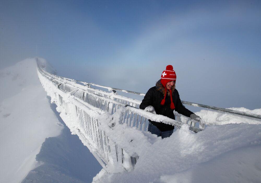 Turistka na visutém mostu Peak Walk ve Švýcarských Alpách