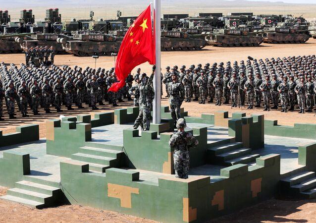 Čínští vojáci na vojenské základně vytahují státní vlajku během vojenské přehlídky na počest 90. výročí založení republiky