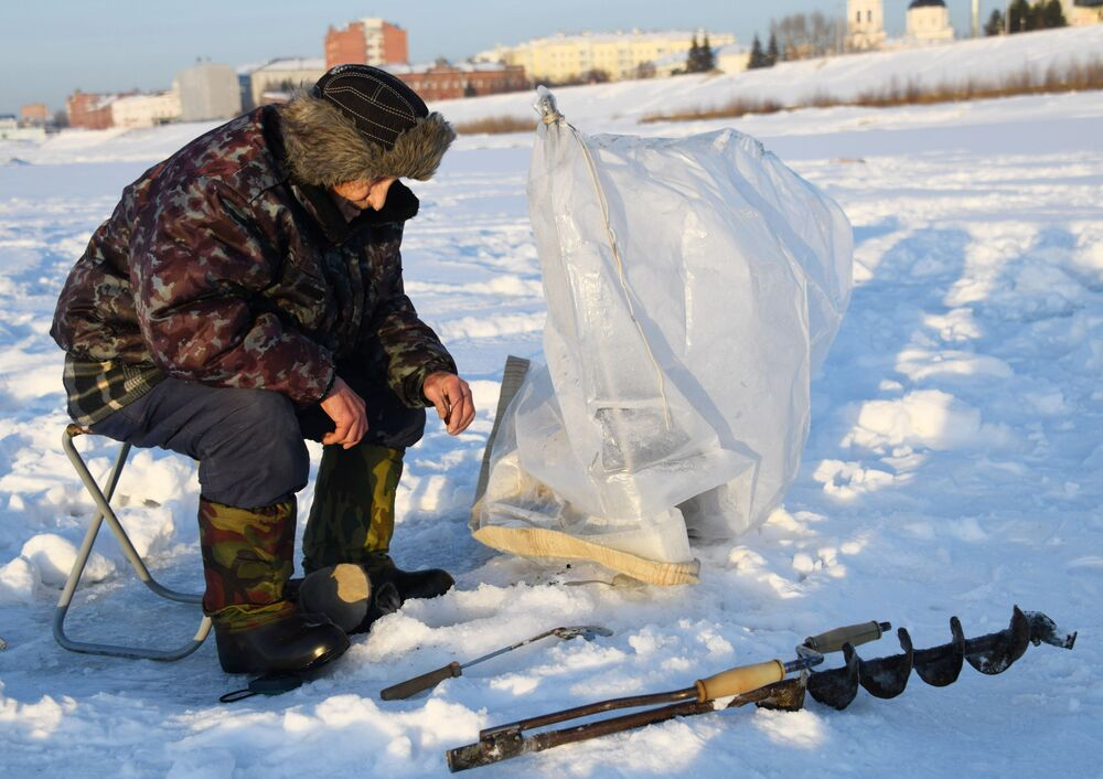 Tradiční ruská zábava: rybolov na dírkách na řece Tom