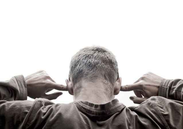 Muž si zakrývá uši rukama
