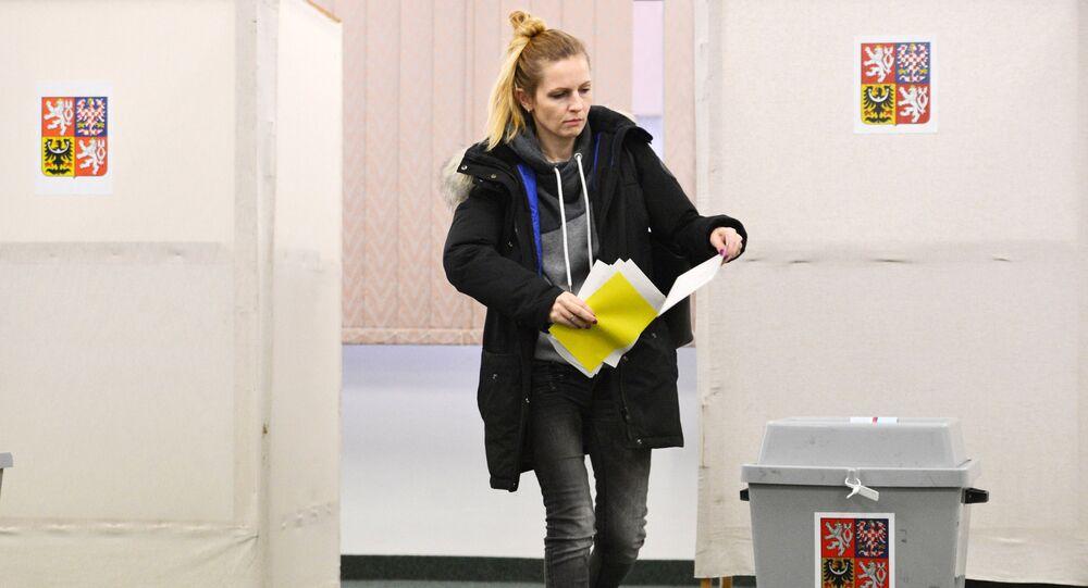 Pražanka hlasuje ve volební místnosti během prvního kola prezidentských voleb v Česku