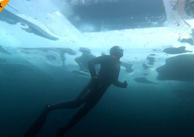 Potápěč plave pod ledem bez jakéhokoli přístroje