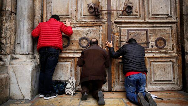 Lidé se modlí u zavřených dveří do Chrámu Božího hrobu v Jeruzalémě - Sputnik Česká republika