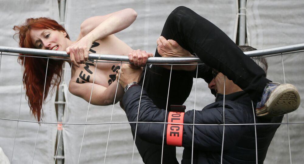 Aktivistka hnutí FEMEN se snaží přelézt plot během akce proti Marine Le Penové na severu Francie.
