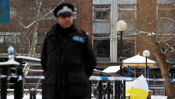 A police officer stands at the cordon near the tent covering the park bench where former Russian intelligence officer Sergei Skripal and his daughter Yulia were found poisoned in Salisbury - Sputnik Česká republika