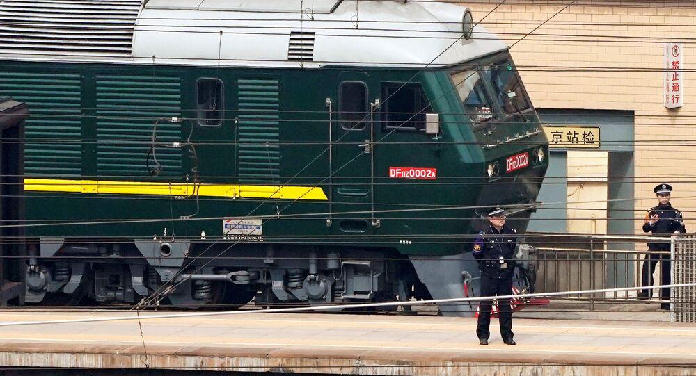 Policista hlídá vlak na nádraží v Pekingu
