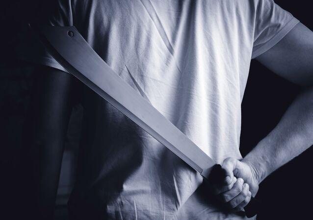 Muž drží za zády mačetu