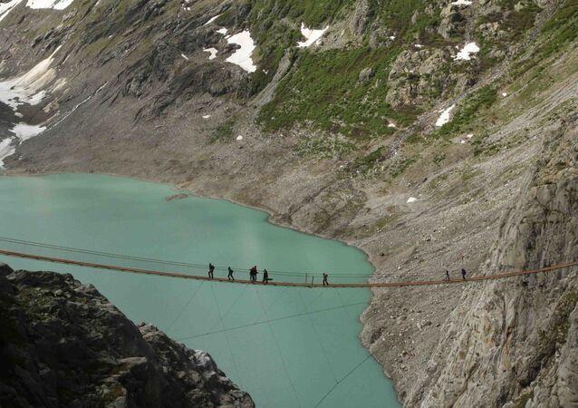 Lidé na mostu v Alpách