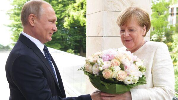 Vladimir Putin daruje květiny kancléřce Angele Merkelové - Sputnik Česká republika