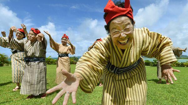 Пожилая женщина в национальном костюме из труппы певцов и танцоров с острова Кохама, префектуры Окинава, Япония - Sputnik Česká republika