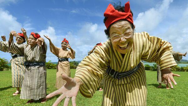Starší žena v národním kroji z souboru zpěváků a tanečníků z ostrova Kokhama, prefektura Okinawa, Japonsko - Sputnik Česká republika