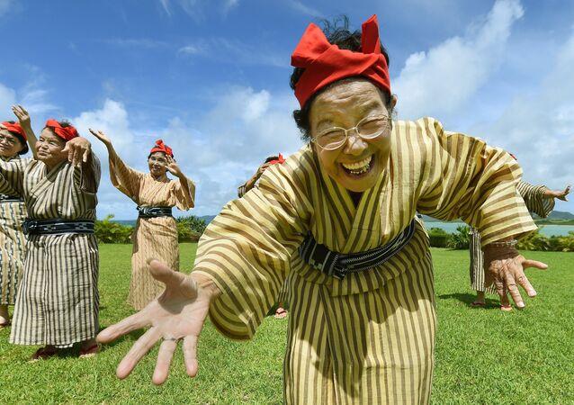Starší žena v národním kroji z souboru zpěváků a tanečníků z ostrova Kokhama, prefektura Okinawa, Japonsko