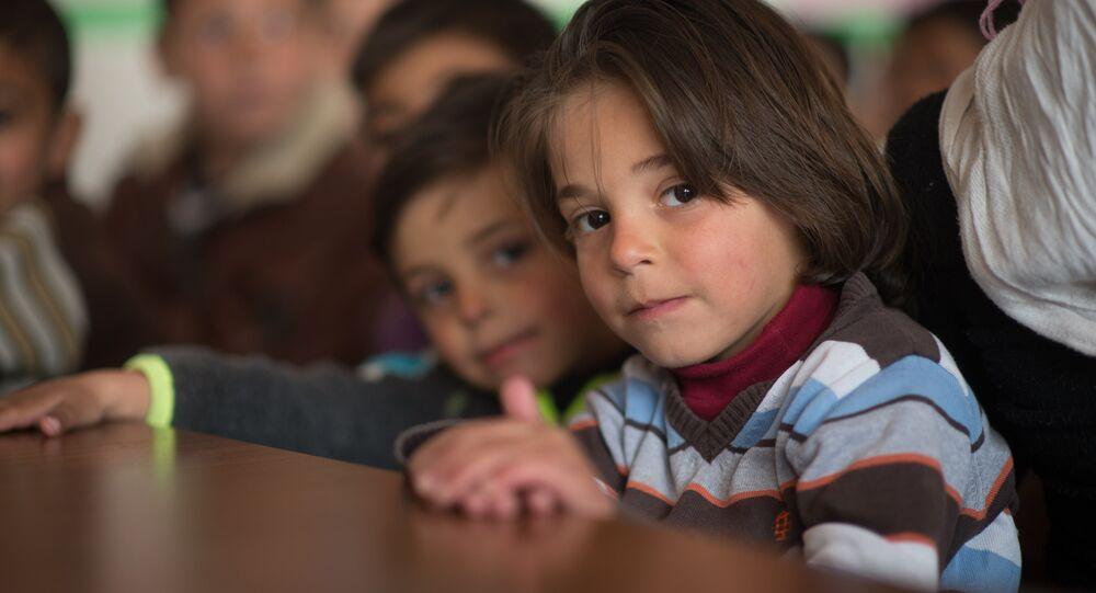 Children in a refugee camp located in a school building, Damascus
