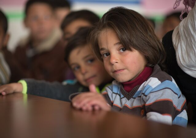 Children in a refugee camp located in a school building, Damascus