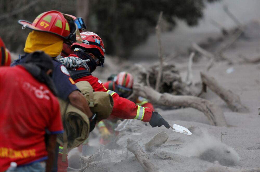 Záchranáři vykopávají popel po erupci sopky Fuego v Guatemale