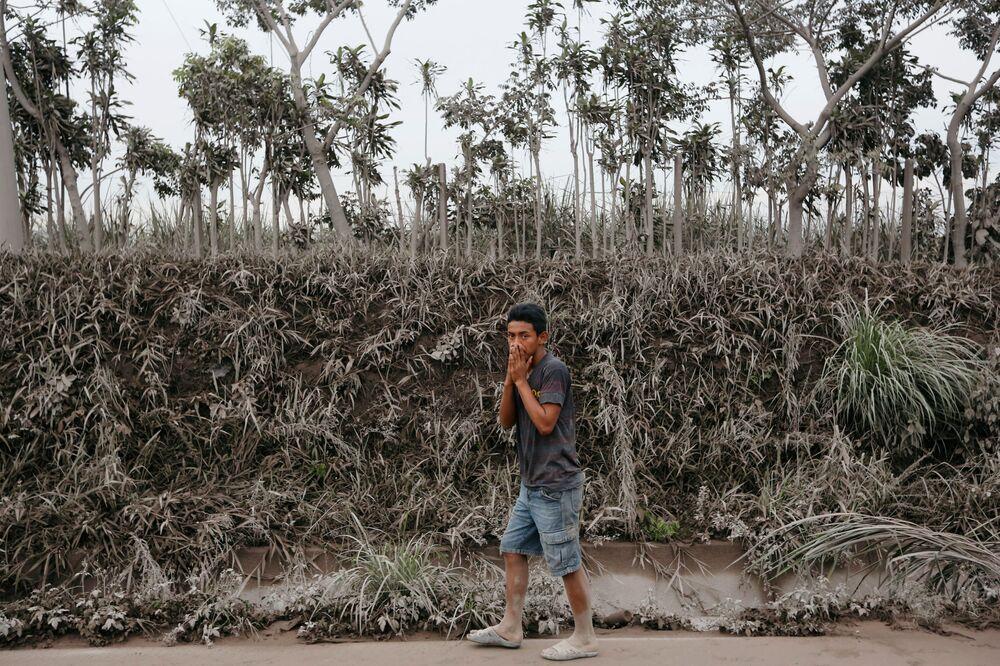 Muž jde oblastí pokryté popelem po erupci sopky Fuego v Guatemale