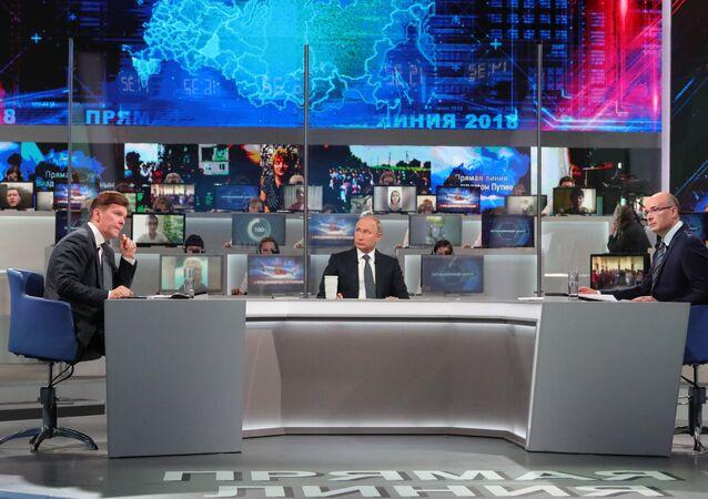 Vladimir Putin a moderátoři Kirill Klejmenov a Andrej Kondrašov
