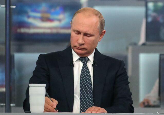 Vladimir Putin si něco zapisuje během Přímé linky