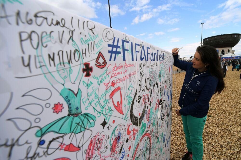 Dívka píše na plakátu přání k festivalu fanoušků Světového poháru 2018 v Kazani