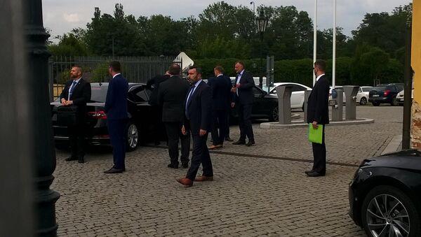 Z tmavých vozů vystupují muži prezidentova kruhu, aby doprovodili hlavu státu k mikrofonu - Sputnik Česká republika