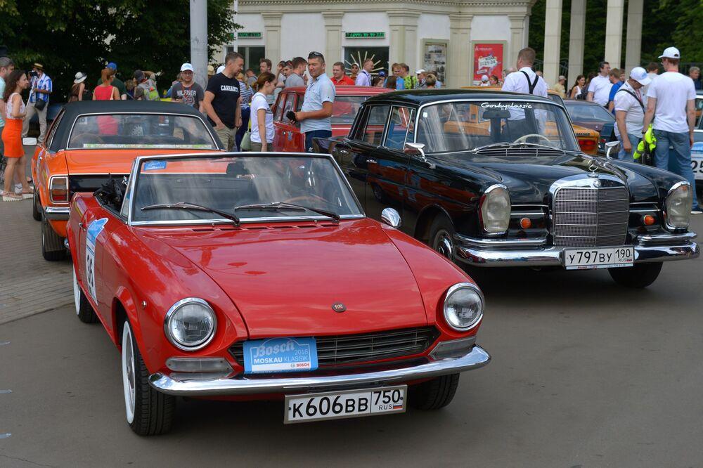 Automobily Fiat 124 Sport Spider (vlevo) a Mercedes-Benz 230S před zahájením rally Bosch Moskau Klassik v Moskvě.