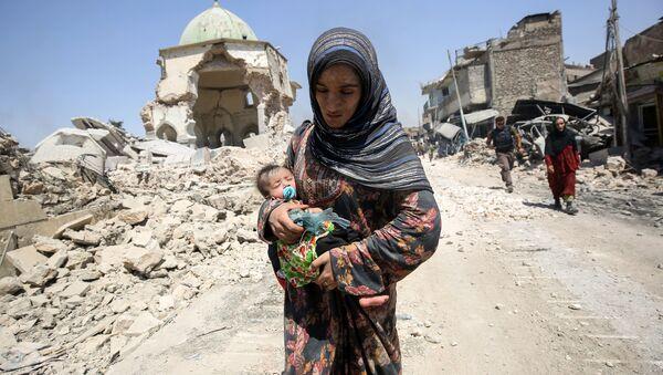 Irácká žena s dítětem před zničenou mešitou Al-Nuri v Mosulu v červenci 2017 - Sputnik Česká republika