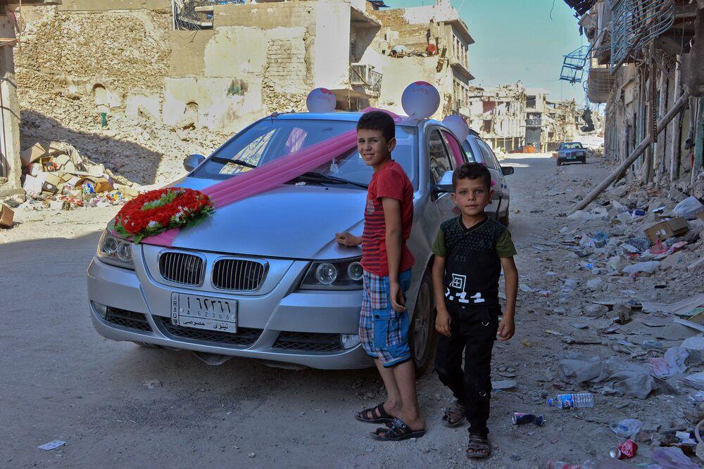 Děti poblíž automobilu, který byl vyzdoben pro první svatbu v Mosulu poté, co byl osvobozen vládními jednotkami. Červenec 2018