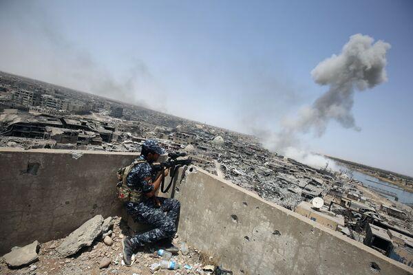 Irácký ostřelovač pozoruje letecké údery mezinárodních koaličních sil pod vedením Spojených států, zaměřených na ISIS, ve starém městě Mosulu, červenec 2017 - Sputnik Česká republika