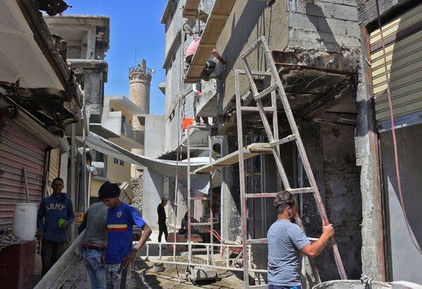 Pracovníci obnovují domy v Mosulu v Iráku v červenci 2018 - Sputnik Česká republika