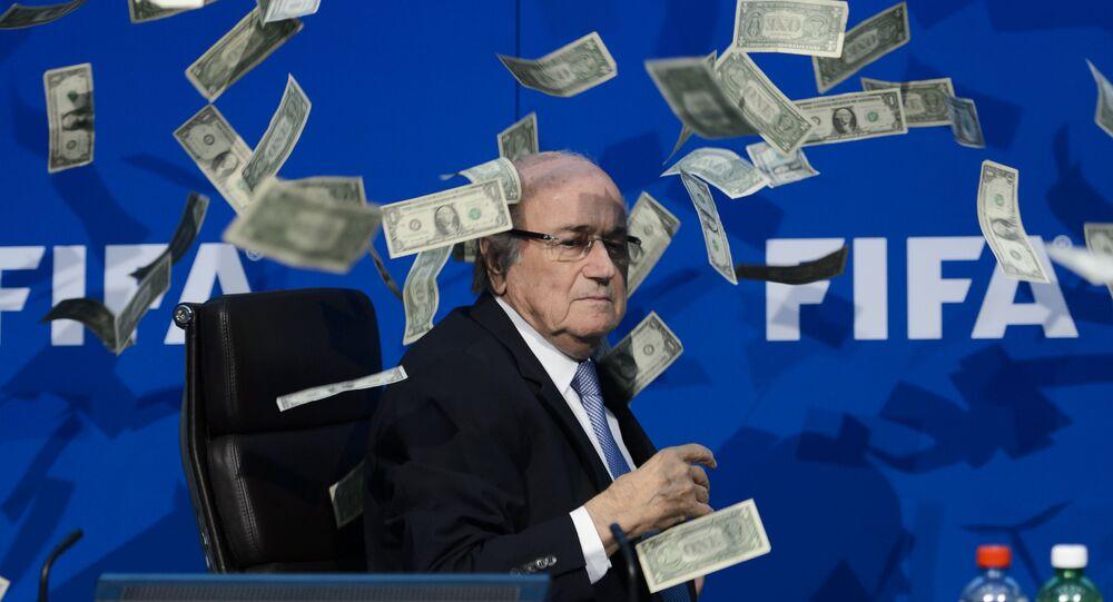 Prezident FIFA Sepp Blatter se dívá na falešné dolary, které házeli protestující během tiskové konference v sidle v Curychu.