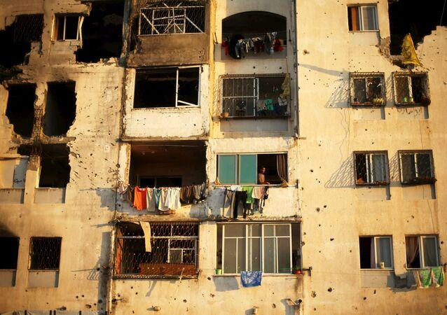 Palestinci se dívají z domu, který byl poškozen před rokem během izraelského ostřelování ve městě Bajt Lahíja, Pásmo Gazy.
