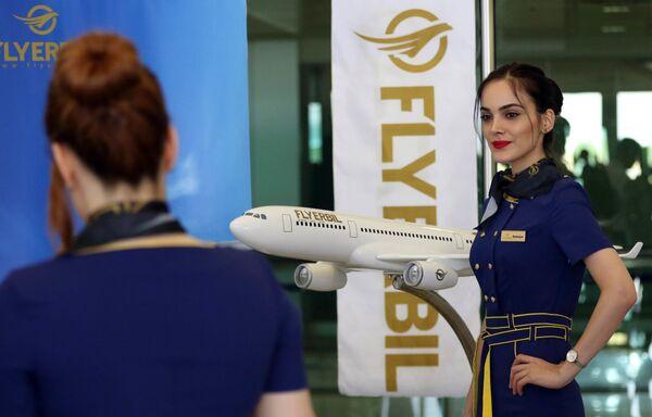 Letuška aerolinek Fly Erbil pózuje u makety letadla na mezinárodním letišti v Erbilu, Irák. - Sputnik Česká republika
