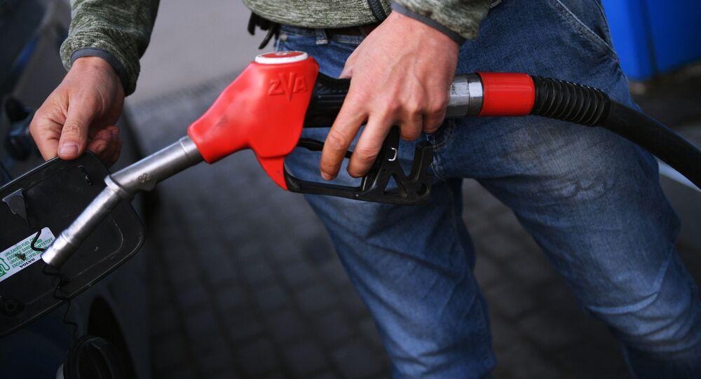 Muž tankuje benzín do auta