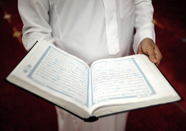 An imam holds the Quran after a prayer at a mosque