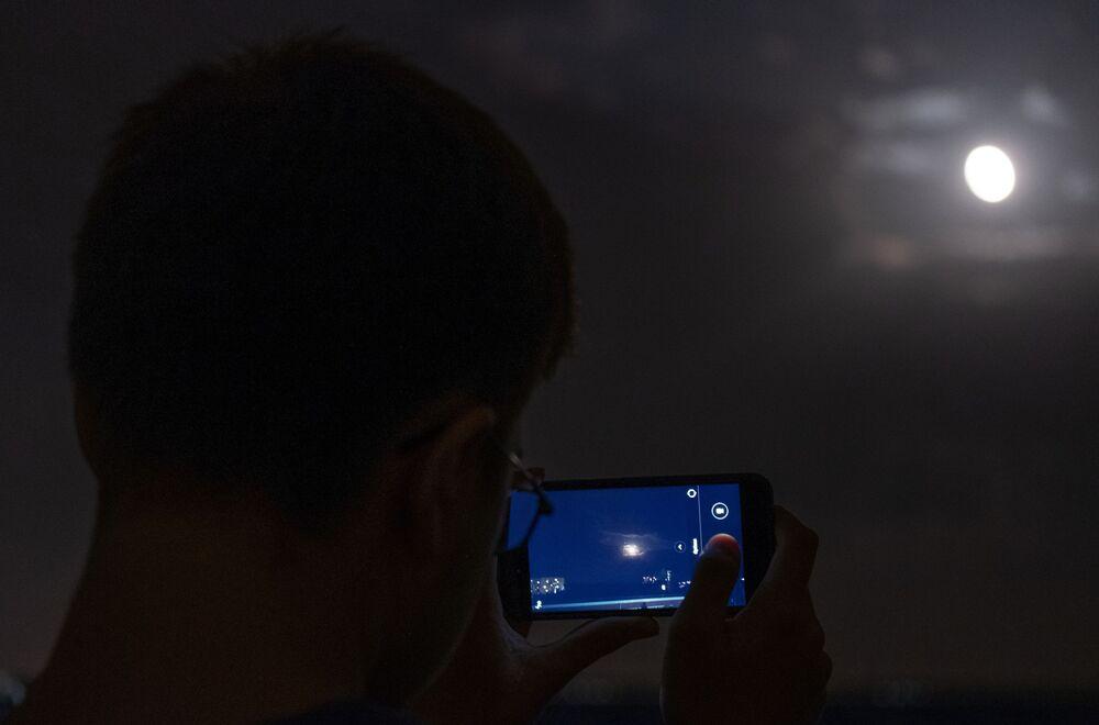 Muž fotografuje měsíc na telefon během úplného zatmění v observatoře Kubanské státní univerzity